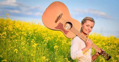 Annemarie mit Gitarre im Rapsfeld
